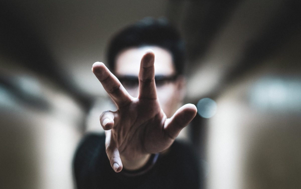 shallow focus photo of person reaching right hand